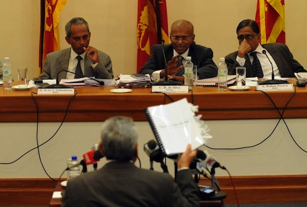 Sri Lankan Defence Ministry Secretary Gotabhaya Rajapakse who spearheaded the succesful military campaign against the Tamil Tiger rebels (C/back to camera) gestures towards the panel led by former Attorney General C.R. de Silva (C/REAR) as he testifies before the Lessons Learnt and Reconciliation Commission in Colombo on August 17, 2010. The Commission was appointed by the Sri Lankan President to review the period between the Norwegian backed ceasefire which went into effect from February 2002 and the end to the military campaign in May last year. Photo taken from JDS