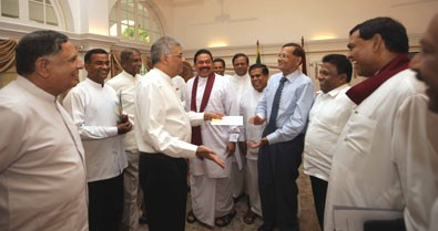 Frenemies? Opposition leader Ranil WIckremasinghe (L) greets External Affairs Minister G.L.Peiris (R) as President Mahinda Rajapakse  and his brother Minister Basil Rajapakse including several other government stalwarts look on.