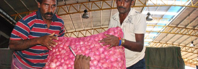 Onion farmers Abeykoon (L) and Jayakumar (R) unloading their crop at the Dambulla Economic Centre