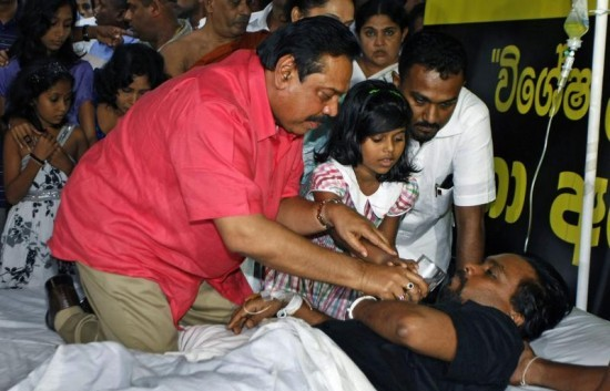 President Rajapakse provides water to Wimal Weerawansa who was on a death fast in front of the UN headquarters in 2010 (File photo)